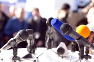 Media Training - group of microphones on table with press in background