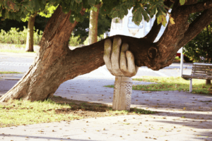 Stone hand holding up tree. PR Agency offers strategic support