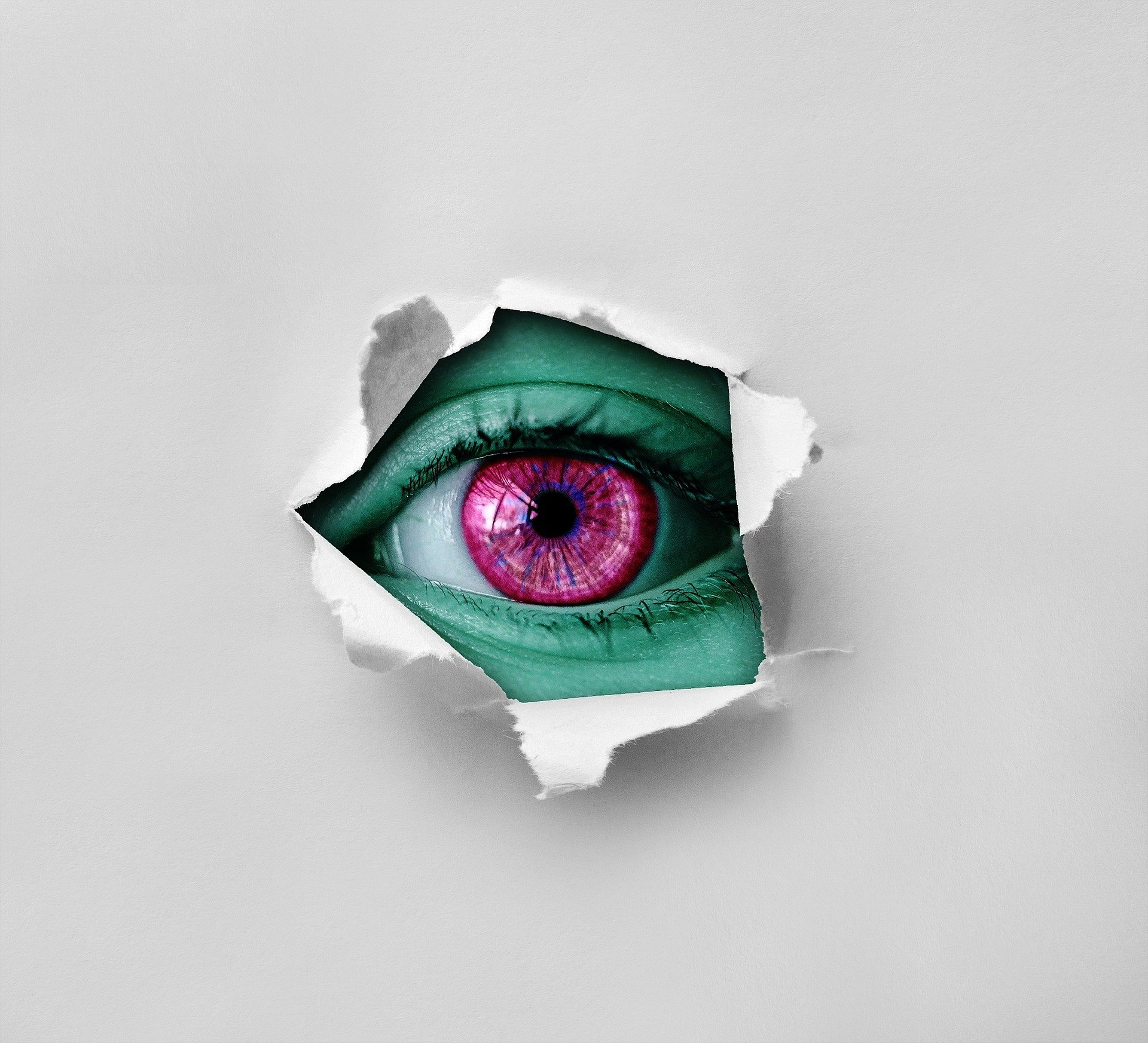 eye looking through torn paper